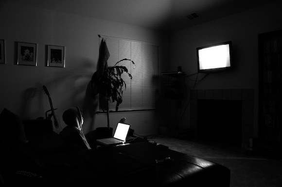 A black-and-white photo of a person watching a television and using a laptop computer.